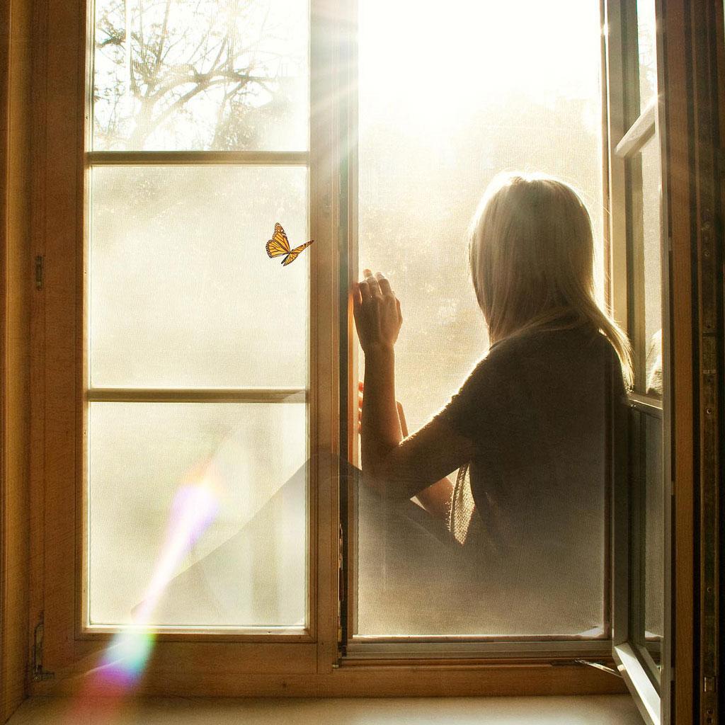 Фото девушка сидит у окна.